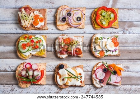 Sandwiches on wooden background, top view. - stock photo