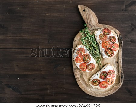 Sandwiches or bruschetta with roasted cherry tomatoes, soft cheese, garlic and herbs on a rustic wooden board over a dark wood background with a copy space. Top view - stock photo