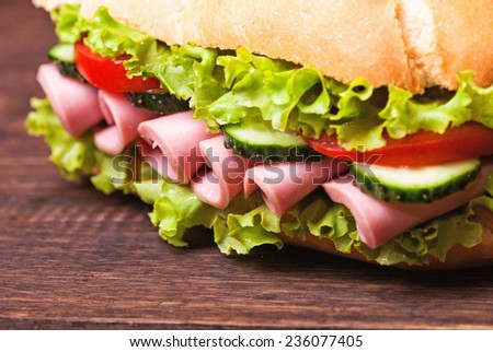 Sandwiches - turkey breast, ham & swiss and salami on a cutting board. - stock photo