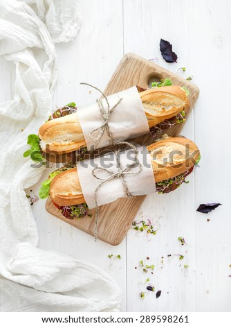 Sandwiches with beef, fresh vegetables and herbs on rustic wooden chopping board over white wood backdrop, top view - stock photo