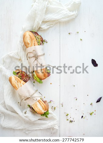 Sandwiches with beef, fresh vegetables and herbs over white wood backdrop, top view, copy space - stock photo