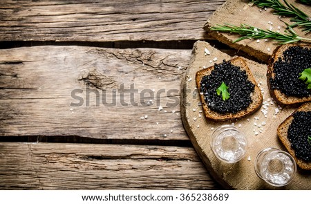 Sandwiches with black caviar and vodka. On a wooden table. Free space for text . Top view - stock photo