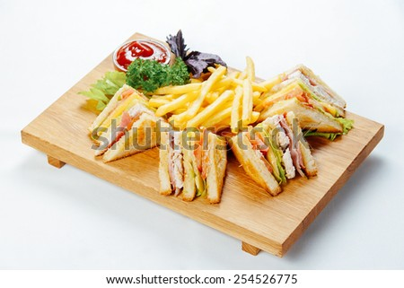 Sandwiches with chicken and french fries on a wooden stand and a white background - stock photo