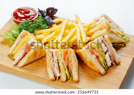 Sandwiches with chicken and french fries on a wooden stand and a white background