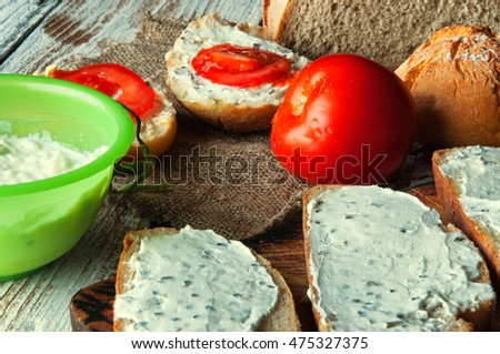 Sandwiches with cream cheese with chives wooden background.