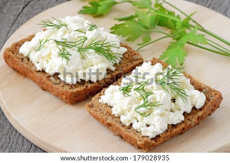 Sandwiches with curd cheese and dill on cutting board - stock photo