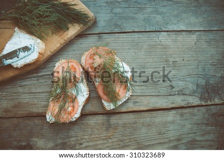 Sandwiches with curd cheese, dill and tomatoes on cutting board. Vintage style. Toned image. - stock photo