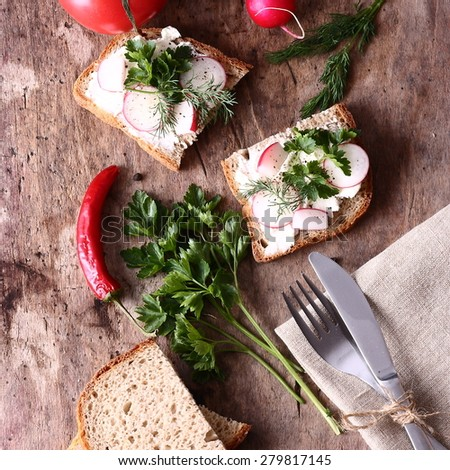 Sandwiches with fresh vegetables and cream cheese on a table - stock photo