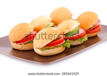 Sandwiches with fresh vegetables, bacon on plate. - stock photo