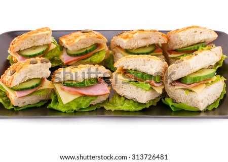 Sandwiches with fresh vegetables, ham and cheese on plate.