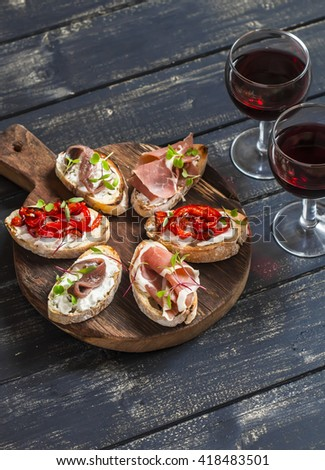 Sandwiches with goat cheese, anchovies, roasted peppers, ham and two glasses of red wine on a wooden rustic board. Delicious snack or appetizer with wine - stock photo