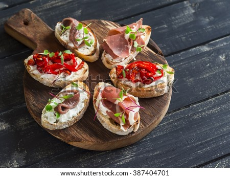 Sandwiches with goat cheese, anchovies, roasted peppers, ham on a wooden rustic board. Delicious snack or appetizer with wine - stock photo