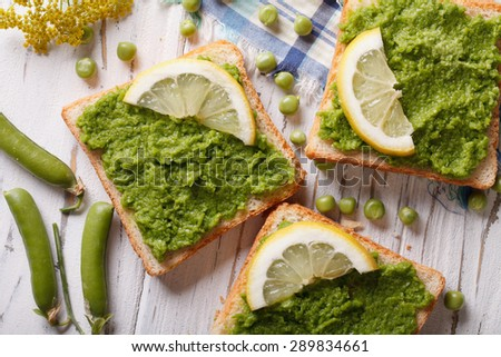 Sandwiches with green peas and lemon close up. horizontal view from above