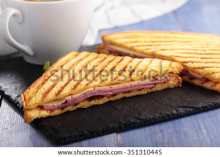 Sandwiches with ham, cheese, lettuce, grilled toasts, and a cup of coffee - stock photo