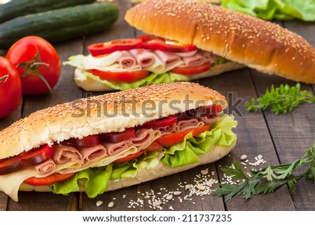Sandwiches with ham, cheese, lettuce, paprika and tomato - stock photo