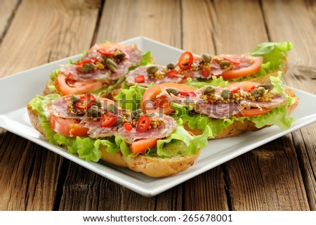 Sandwiches with ham, salad leaves, chili, tomatoes, capers, french mustard in white plate on wooden background - stock photo