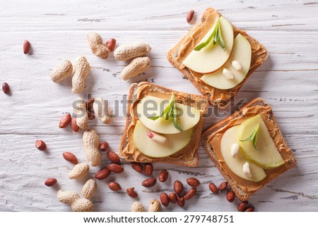 sandwiches with peanut butter and an apple on the table close-up. horizontal top view  - stock photo