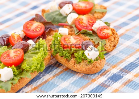 Sandwiches with rusks, vegetables, olives and feta cheese on colorful tablecloth.