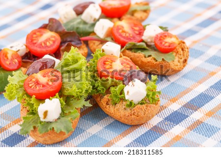 Sandwiches with rusks, vegetables, olives and feta cheese on colorful tablecloth. - stock photo