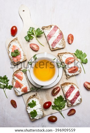 sandwiches with salmon and salami, parsley tea and lunch on wooden rustic background top view - stock photo