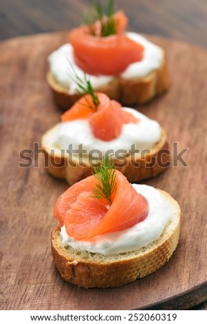 Sandwiches with salmon on wooden cutting board - stock photo