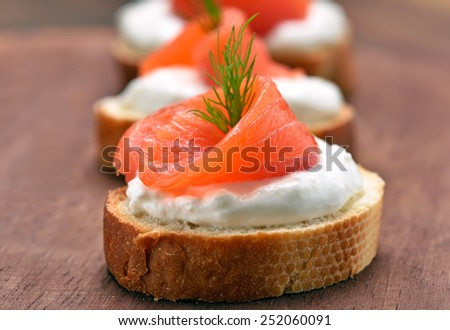 Sandwiches with salmon on wooden cutting board, close up view - stock photo