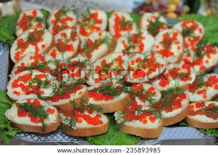 Sandwiches with salmon red caviar on a table. Red caviar sandwiches on plate. macro beautifully served banquet table, bread fruit.  Shallow DOF - stock photo