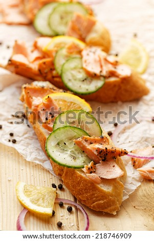 Sandwiches with smoked salmon, cucumber, lemon and black pepper - stock photo
