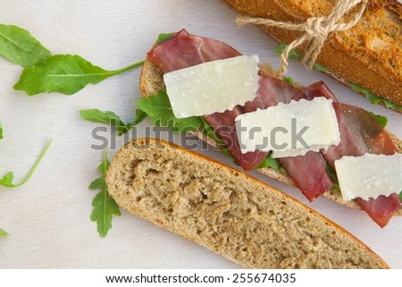 Sandwiches with whole grain bread, rucola,parmesan cheese and bresaola. Free space for a text. - stock photo