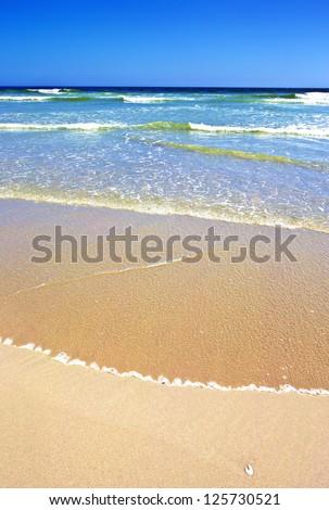 Sandy beach and ocean on a sunny day - stock photo