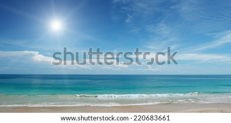 Sandy beach and sun in blue sky                                     - stock photo