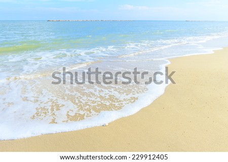 Sandy beach backdrop with turquoise water and bright sun light. Summer holidays concept. - stock photo