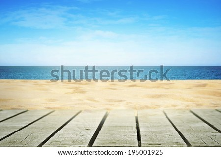 Sandy beach on sunny day with wooden walkway - stock photo