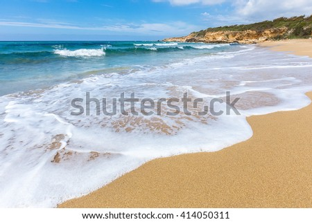 Sandy beach sea waves and mountain at greek coast
