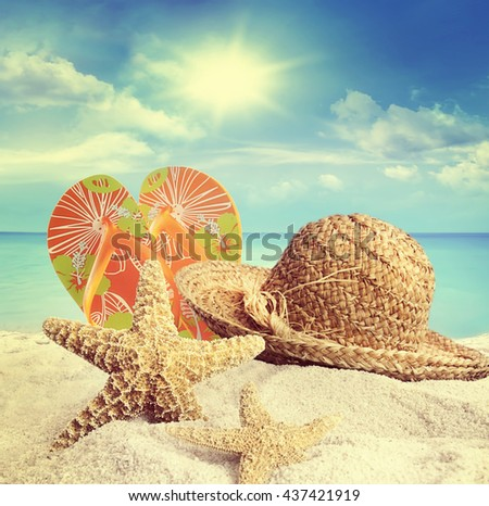 Sandy beach, straw hat and starfish in summer - stock photo