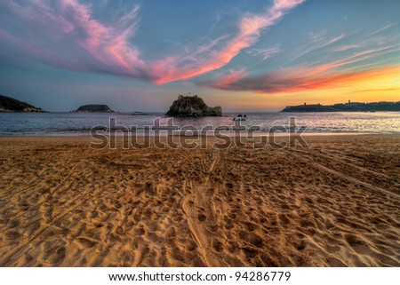 Sandy beach sunset with dramatic clouds - stock photo