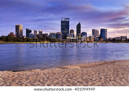 Sandy beach to Perth city CBD at sunrise when still nobody around and calm water flows in Swan river.