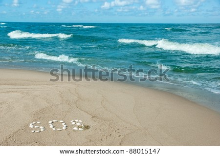 "sandy beach with a word ""SOS"" written with seashells - need for help at the seaside - stock photo"