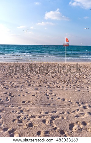 sandy beach with lots of footprints and a blue sky with clouds