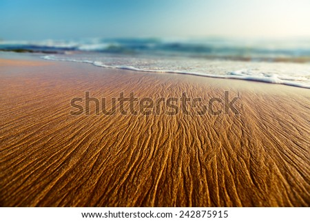 Sandy beach with pattern on the surface at sunset - stock photo