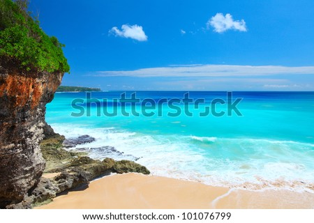 Sandy beach with rocky mountains and clear water of Indian ocean at sunny day. Bali, Indonesia - stock photo
