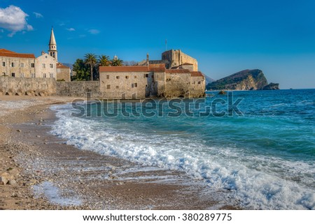 Sandy beaches and turquoise waters next to the old walled city of Budva, one of the oldest settlements on the Adriatic coast, Montenegro - stock photo