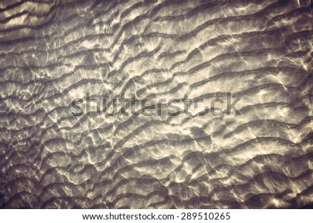 sandy bottom with reflecting sunlight from water ripples. Old fashioned style photography with darken edges