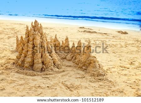 sandy castle at the sea edge - stock photo