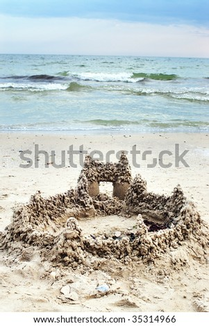 Sandy castle on the beach with blurred stormy sea - stock photo
