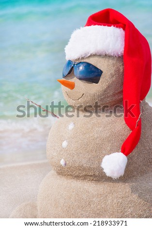 Sandy christmas snowman in red santa hat and sunglasses at sunny beach. Holiday concept for New Years Cards. - stock photo