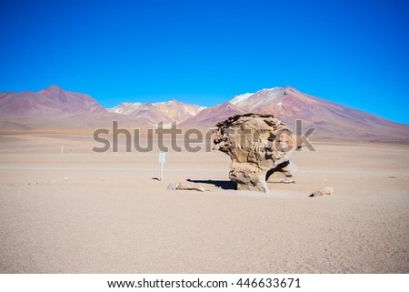 """Sandy desert and scenic rock formation, known as """"Rock Tree"""", on the Andean highlands. Road trip to the famous Uyuni Salt Flat, among the most important travel destination in Bolivia. - stock photo"""