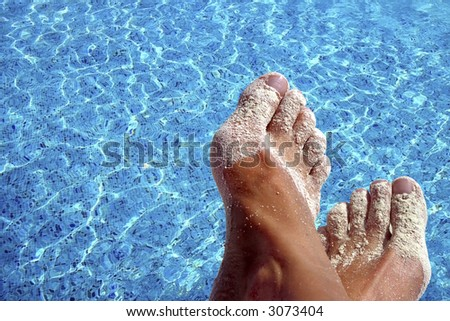Sandy feet with blue pool water as background - stock photo