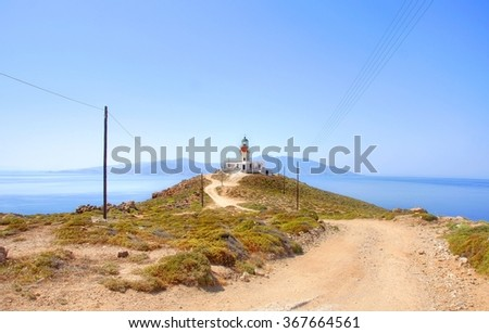 sandy road leads to a old lighthouse at the shoreline on the Island of Mykonos, Greece - stock photo