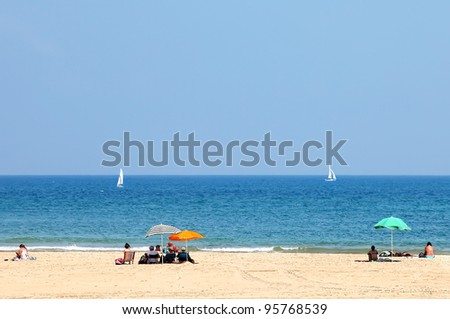 Sandy sea beach and people sitting under the beach color umbrellas.Tel-Aviv. Israel - stock photo
